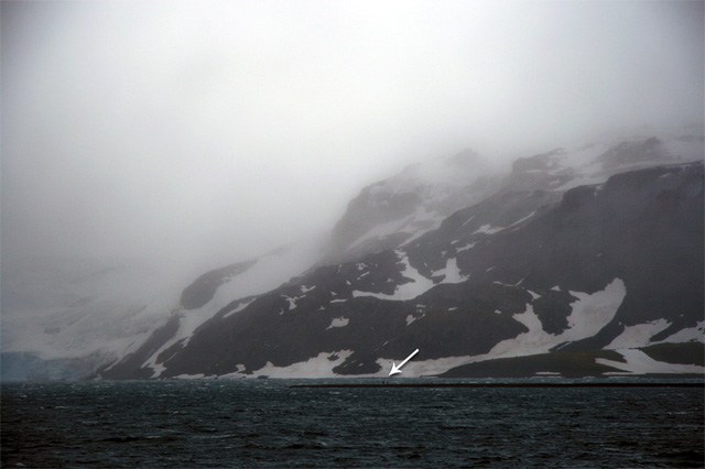 Storms in this region form quickly, and within a few minutes the wind increases, pulling the ship against its anchors and sending down cold, driving rain. (To indicate the immense size of this place, the white arrow in this photo is pointing to one of our landing parties; tiny figures in a remote, unforgiving land.)